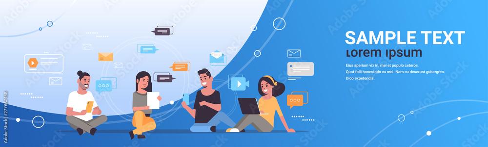 Fototapeta young people using digital gadgets social network communication technology concept men women group chatting online full length flat horizontal copy space