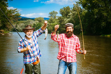 Fishing Became A Popular Recreational Activity. Fishing. Generations Ages: Grandfather And Father. Grandfather And Boy Fishing Together.