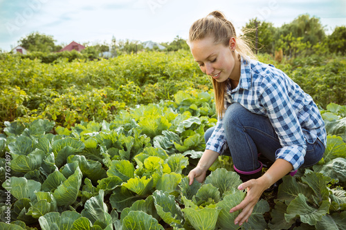 Young farmer working at her garden in sunny day Wallpaper Mural