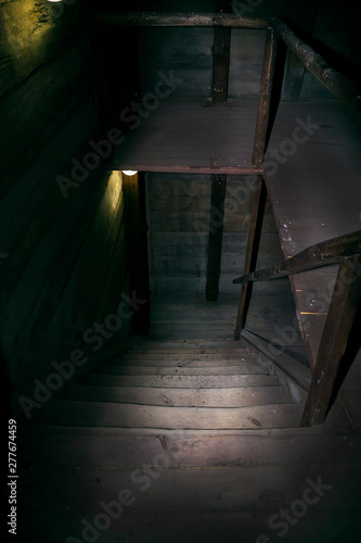 Darkness and horror in a ghostly building. Inside on a dark wooden staircase with steps down to the basement of an old abandoned house with black walls mystical light from a dim lamp on the floor