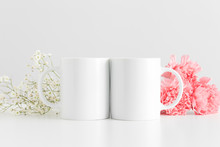 Two Mugs Mockup With A Bouquet Of Pink Carnations And A Gypsophila On A White Table.