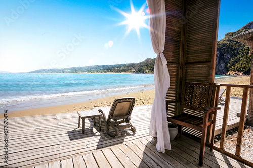 Wooden terrace on beach and sunbed