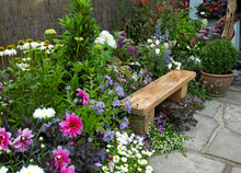 A Traditional Thatched Cottage Garden Designed To Creat A Calming And Relaxing Space With Colourful Flowers And Seating