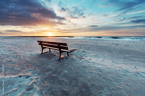 Poster de jardin Mer coucher du soleil Lonely bench on the beach at sunset with view on the sea