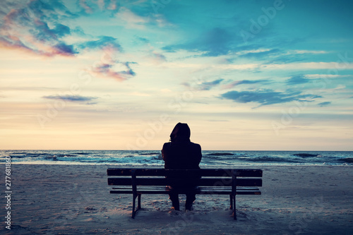Foto Man in hood sitting on a lonely bench on the beach