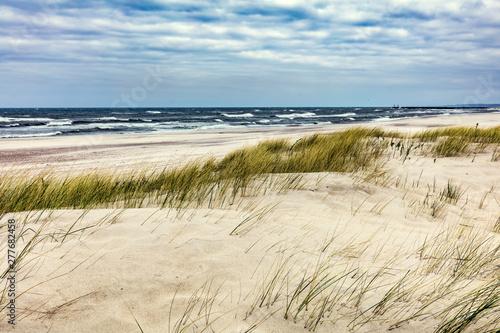 Obraz Trawiaste wydmy i Morze Bałtyckie o zachodzie słońca - fototapety do salonu