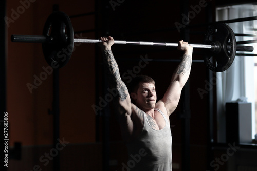 Fotografie, Obraz  male bodybuilder doing exercises with a barbell