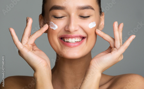Foto op Canvas Spa Happy Woman Applying Cosmetic Cream On Her Face