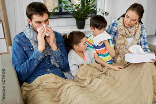 family, health problem and people concept - ill father, mother, daughter and son blowing nose at home