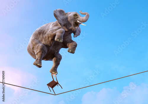 Fotografiet Elephant balancing on the tightrope high in the sky above clouds