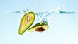 canvas print picture - Fresh ripe avocado halves falling in water