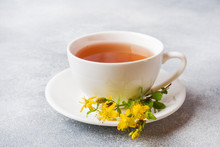 Cup With Herbal Tea From Petals Flowers Hypericum On Grey Background. Copy Space.