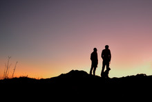 A Dad With His Son Standing With Their Dog On A Ridge Watching The Sun Rise