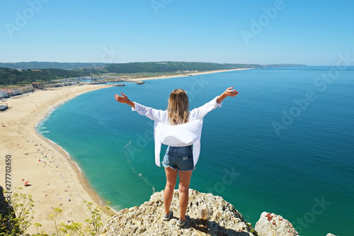 Montage in der Fensternische Blau Young woman wearing oversized cotton shirt enjoying the panoramic top view of famous Nazare beach, Atlantic ocean Algarve, Portugal. Copy space for text, background. Hello summer concept.