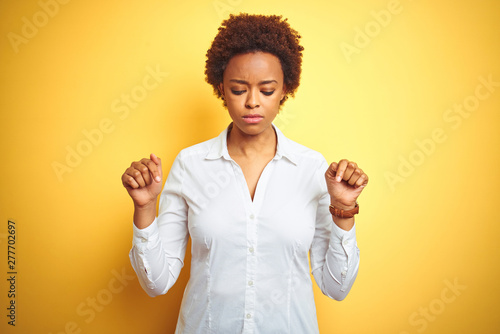 Obraz na plátně African american business woman over isolated yellow background Pointing down looking sad and upset, indicating direction with fingers, unhappy and depressed
