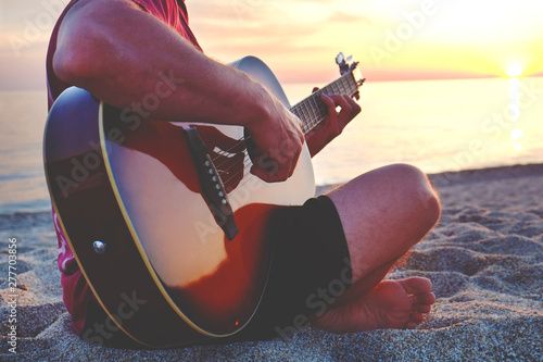 Young man wearing purple tie dye t-shirt playing dreadnought parlor acoustic guitar on beach at beautiful sunset time Canvas Print