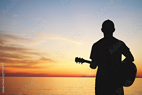 Young man wearing purple tie dye t-shirt playing dreadnought parlor acoustic guitar on beach at beautiful sunset time. Fit guitarist w/ sunburst instrument by the sea. Background, copy space, close up - 277703872