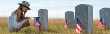 Panoramic Shot Of Kid In Straw Hat Covering Face While Sitting Near Headstones With American Flags