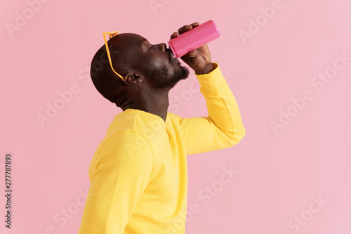 Fotografie, Tablou Drink. Black man drinking soft drink on pink background portrait