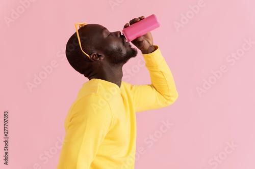 Fototapeta Drink. Black man drinking soft drink on pink background portrait