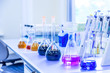 Chemical analysis, pharmacology and laboratory concept. Flasks with colored liquid reagents in a science laboratory. Blue toned