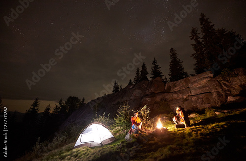 Fototapeta Night summer camping in the mountains. Happy couple hikers having a rest together, sitting beside campfire and glowing tourist tent. On background big boulder, forest and beautiful night starry sky. obraz na płótnie