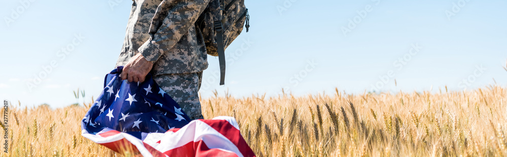 Fototapeta panoramic shot of patriotic soldier in military uniform holding american flag while standing in field