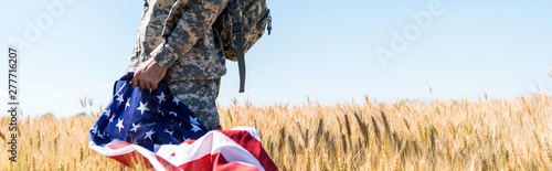 Fotografiet panoramic shot of patriotic soldier in military uniform holding american flag wh