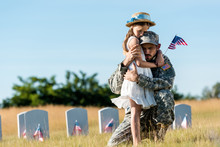 Military Man With Closed Eyes Hugging Daughter Near Headstones In Graveyard