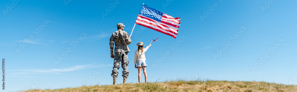 Fototapeta panoramic shot of kid and military father holding american flags