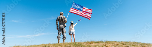 Obraz panoramic shot of kid and military father holding american flags - fototapety do salonu