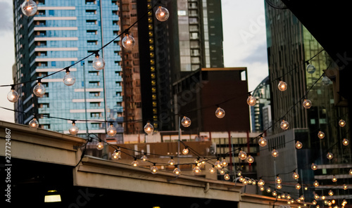 Fotografering A hanging string of lights at Queen Victoria Markets with the skyline of Melbour