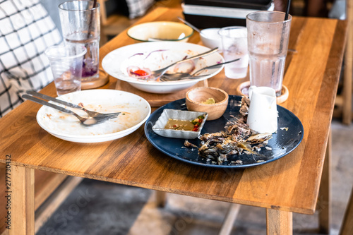 Fotomural Dirty dishes of leftover food on table in restaurant.