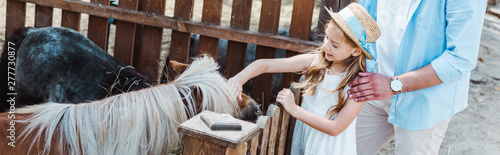 Canvas Print panoramic shot of cheerful kid touching pony while standing near father in zoo
