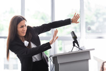 Frightened Lecturer, Suffering From Fear Of Public Speaking, Gesturing With Hands While Standing On Podium Tribune