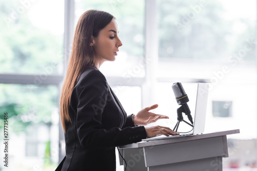 attractive, confident lecturer gesturing while speaking from podium tribune Canvas Print
