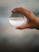 Crop View Of Little Female Child With Brown Hair Holding Glass Ball On Background Of Waves