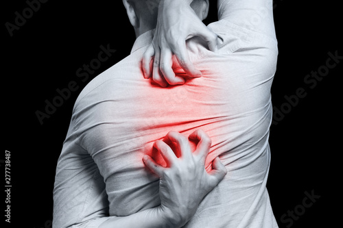 Man scratching his back, isolated on black background - 277738487