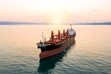 Aerial view of high-speed sea vessel for transportation of a cargo vessel at high speed is drifting near the seaport of the city at sunset. Ship on the background of blue sea water. Import, export