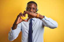 African American Operator Man Working Using Headset Over Isolated Yellow Background Smiling In Love Showing Heart Symbol And Shape With Hands. Romantic Concept.