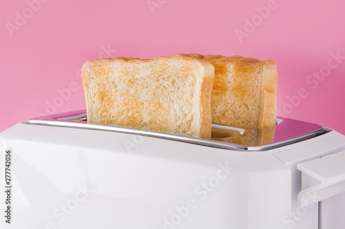 Fotomural Toasted toast bread in white toaster on pink background