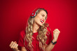 canvas print picture - Young beautiful woman wearing headphones over red isolated background very happy and excited doing winner gesture with arms raised, smiling and screaming for success. Celebration concept.
