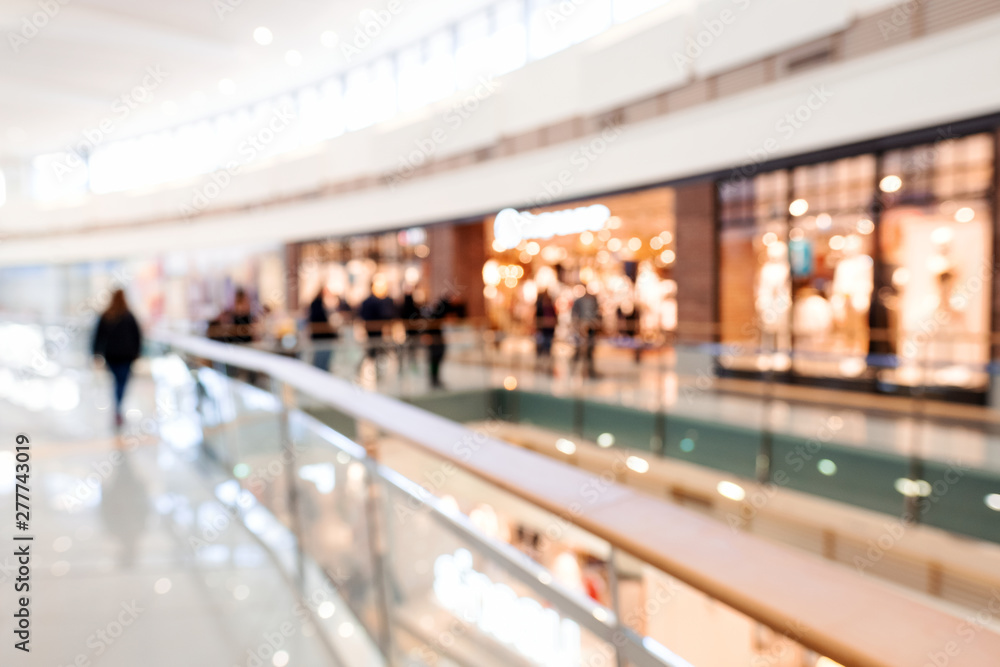 Fototapeta Blurred big sales on Black Friday. A long light floor in the mall with shops for buyers. Sale of clothing in a modern shopping center. The main background for the design. Shopping. Copyspace