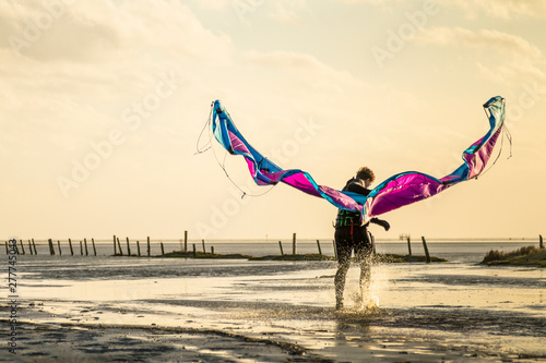 Man with kite standing on beach during sunset