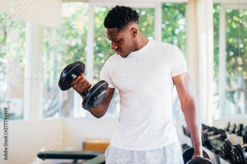 Fotografie, Obraz  Young African American man standing and lifting a dumbbell with the rack at gym