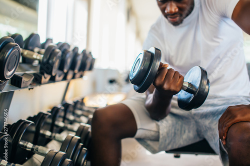 Carta da parati Young African American man sitting and lifting a dumbbell close to the rack at gym
