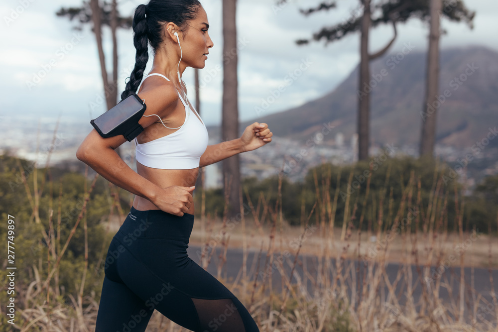 Fototapety, obrazy: Woman athlete running on country road