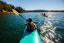 A Group Of Kayakers Paddle Under Blue Skies Through Wasp Passage Near Shaw Island (in The Distance) During A 3-day Tandem Kayaking Trip In The San Juan Islands Of Northwest Washington.