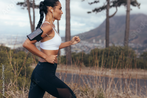 obraz PCV Woman athlete running on country road
