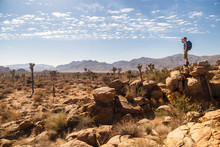 Hiker Looking At Joshua Tree National Park While Standing On Rock